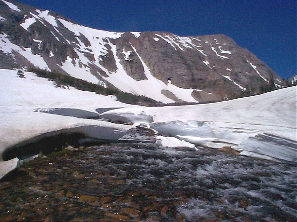 A snowfield erroded by the rushing water.