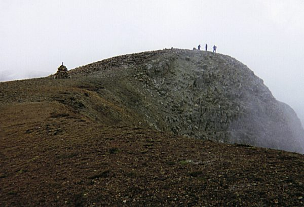 Hikers on the summit of Mount Sopris with the memorial visible at center-left.